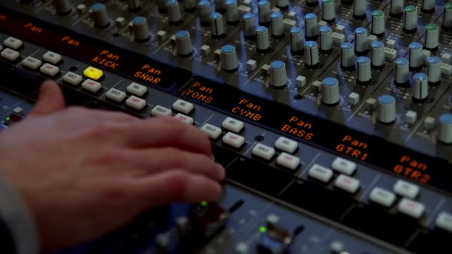 CU PAN Shot of Hand pushing buttons of sound mixing desk / United States