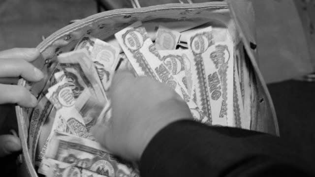 CU Shot of hand reaching into sack of money