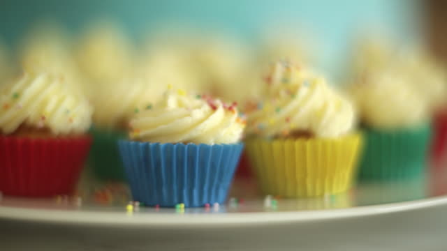 CU Shot of hand sprinkling multicolored mini candy balls onto frosting icing mini cup cakes / Auckland, New Zealand