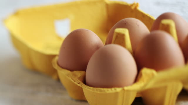 cu  pan shot of hand taking egg from yellow carton / london, united kingdom  - lift stock videos & royalty-free footage