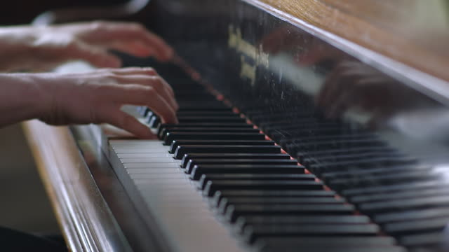cu shot of hands and fingers playing piano / united kingdom - pianist stock-videos und b-roll-filmmaterial