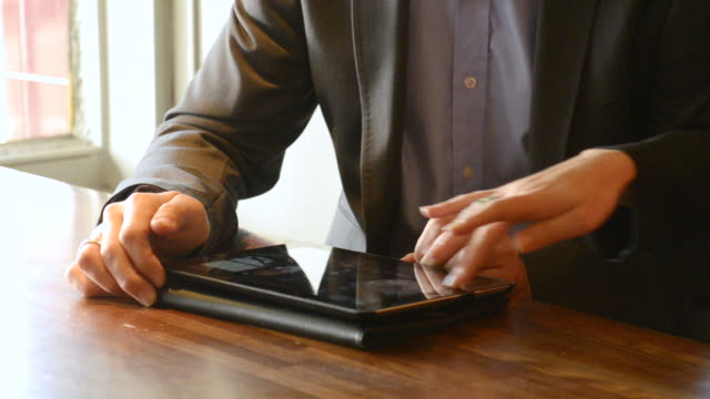 CU Shot of hands of younger man and younger woman with tablet computer in pub / London, England, United Kingdom