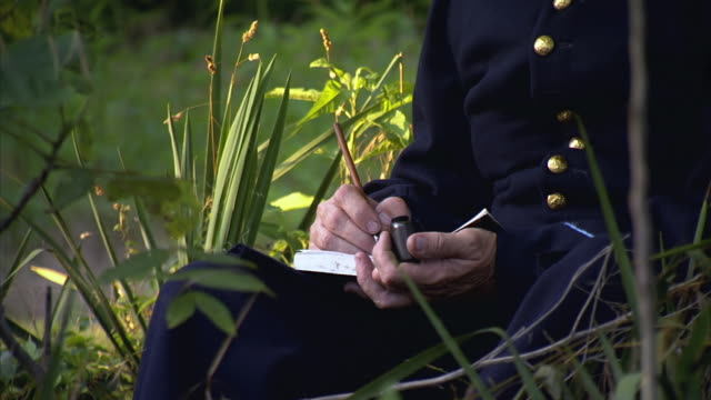 MS PAN TU Shot of Hands to face as Union soldier writes letter while sitting under tree / Middleburg, Virginia, United States