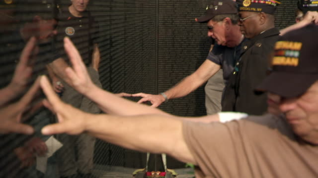 ms shot of hands touch vietnam veterans memorial wall / washington, district of columbia, united states - vietnam veterans memorial video stock e b–roll