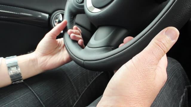 CU Shot of hands touching car steering wheel / Washington, DC, United States