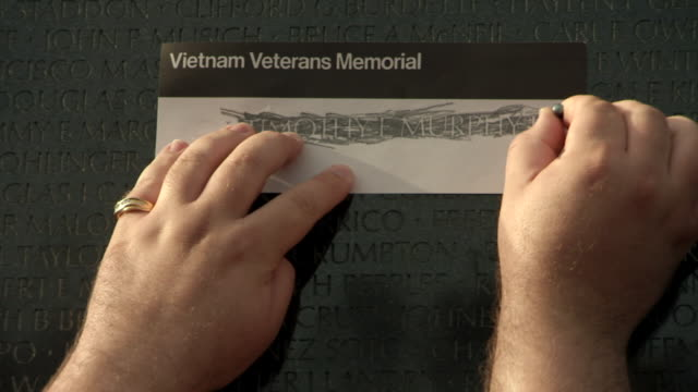CU Shot of hands trace name engrave on Vietnam Veterans Memorial Wall / Washington, District of Columbia, United States