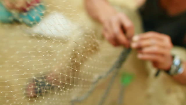 stockvideo's en b-roll-footage met cu r/f zi zo slo mo shot of hands working on net / muang ngoi, luang prabang, laos - infaden