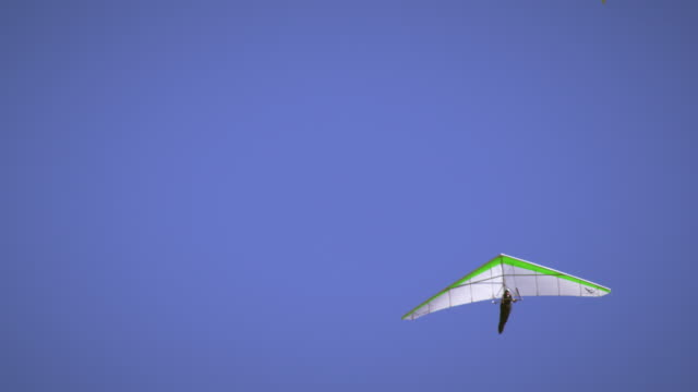 Shot of hang glider and paraglider in the air near eachother.