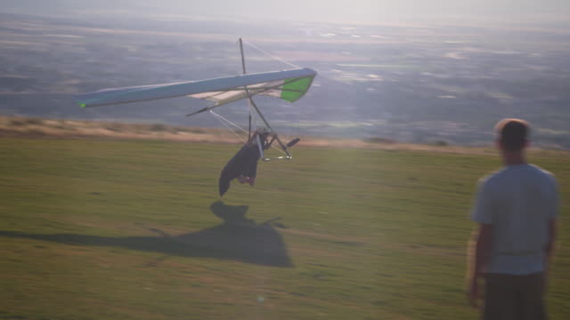 Shot of hang glider slowing and coming to a stop on top of a hill.