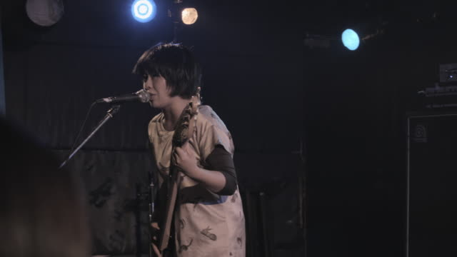 ms pan shot of hard core band playing on stage / shibuya, tokyo, japan - 歌う点の映像素材/bロール