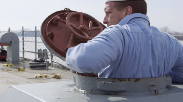 cu shot of hatch door on lst deck opens and navy sailor comes out on deck / evansville, indiana, united states - heckklappe teil eines fahrzeugs stock-videos und b-roll-filmmaterial