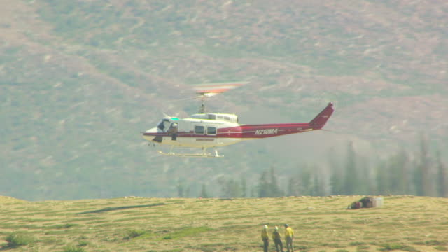 cu aerial shot of helicopter landing beside three waiting firemen in bob marshall wilderness / montana, united states - rescue worker stock videos and b-roll footage
