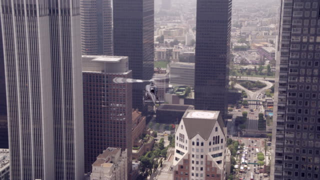 ms aerial ts shot of helicopter moving over city through building and landing on top of tall modern building - landen stock-videos und b-roll-filmmaterial