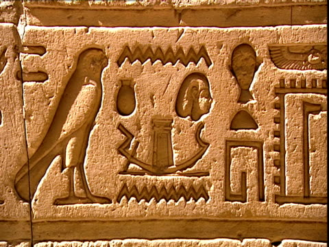 vidéos et rushes de shot of hieroglyphs in the temple of edfu, showing a high-prow boat with a shrine in the centre, a falcon , a head and wavy lines symbolising water. - couvre chef
