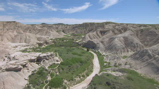 WS AERIAL Shot of High over rock formations and ravine at Toadstool Geologic Park / Nebraska, United States