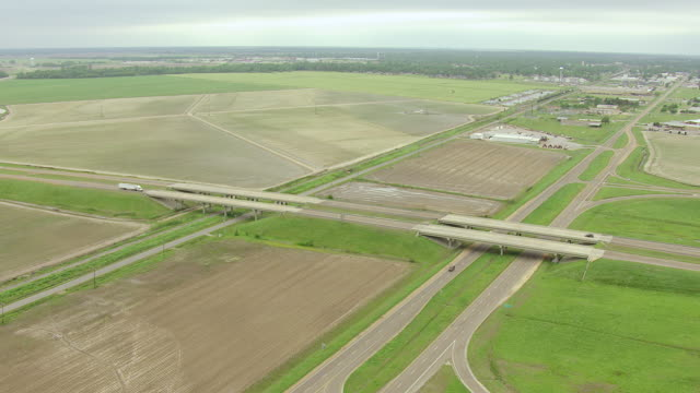 WS AERIAL Shot of highway 61 and highway 49 crossroads with trucks and cars driving / Clarksdale, Mississippi, United States