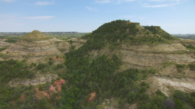 MS AERIAL Shot of Hill to reveal wide landscape in Badlands in Theodore Roosevelt National Park / North Dakota, United States