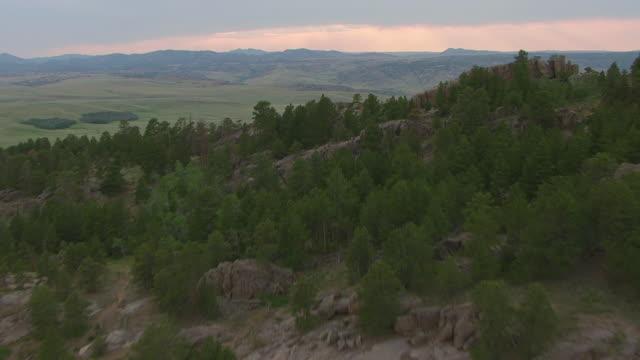 vídeos y material grabado en eventos de stock de ms aerial shot of hills to reveal clouds in sky and sunset at guernsey ruts in platte county / wyoming, united states  - expansión hacia el oeste