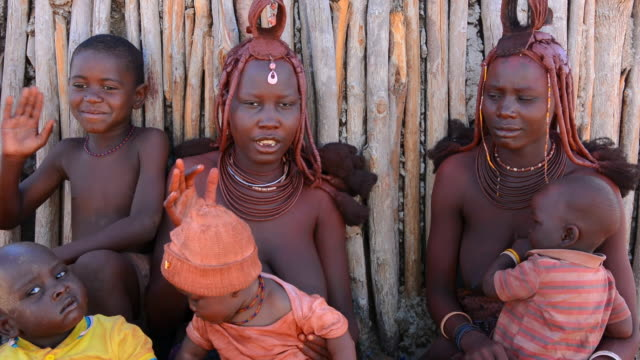 CU Shot of Himba tribe two young women friends with braids and traditional dress in desert of Hartmann Berge / Namib Desert, Namibia, South Africa