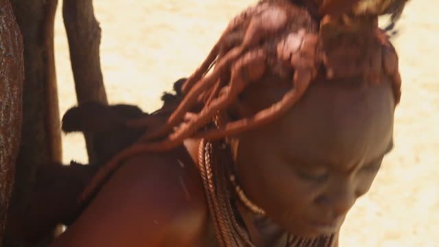 stockvideo's en b-roll-footage met cu shot of himba woman with clay in her hair and aboriginal necklaces / himba, kunene, namibia - wiese