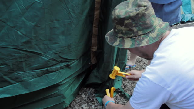 cu shot of hitting nail with hammer, setting tent / okutama, tokyo, japan - キャンプする点の映像素材/bロール