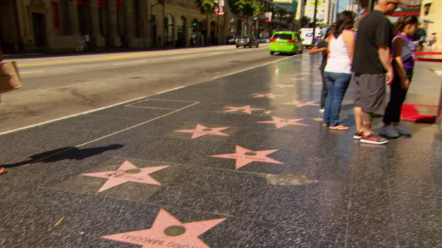 CU TU TD Shot of Hollywood walk of fame - Britney Spears with people walking and traffic moving on road / Los Angeles, California, United States
