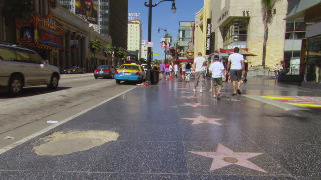 ms shot of hollywood walk of fame with people walking and traffic moving on road / los angeles, california, united states - ウォークオブフェーム点の映像素材/bロール