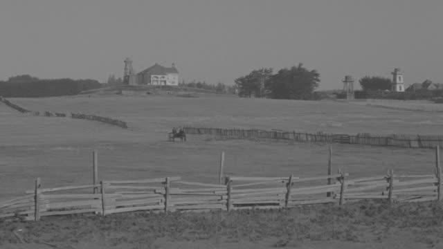 vidéos et rushes de ws ts pan shot of horse and buggy moving across farmland - voiture hippomobile