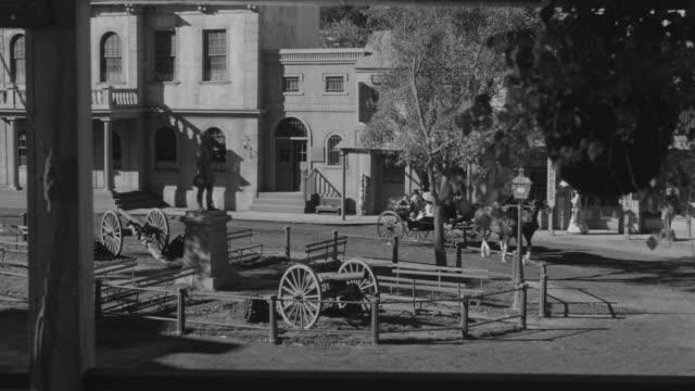 vídeos y material grabado en eventos de stock de ms ts shot of horse and carriage riders in town - grupo pequeño de animales