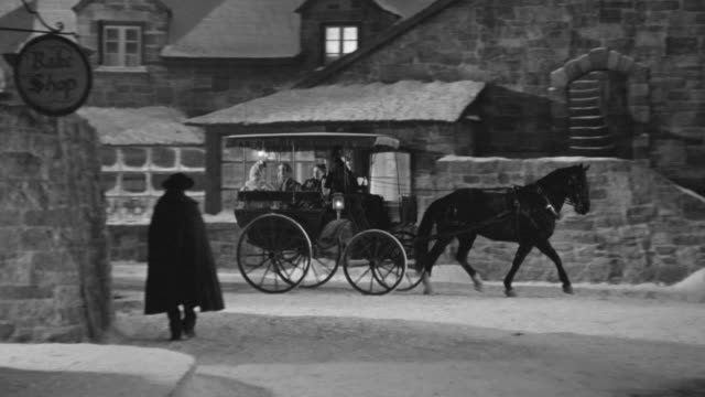 ws pan shot of horse and carriage riding through small town with stone buildings and some people walk about shops - kutsche stock-videos und b-roll-filmmaterial