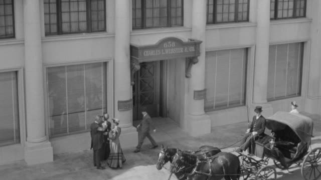 ms shot of horse and carriage sit in front of old publishing house building and people walking and talking on sidewalk - kutsche stock-videos und b-roll-filmmaterial