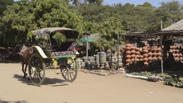 MS Shot of Horse carriage driving past ceramic shop / Bagan, Mandalay Division, Myanmar