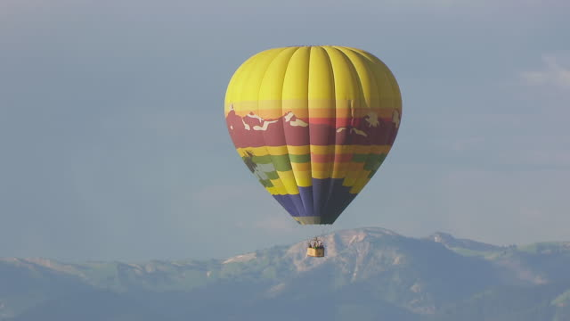 vídeos y material grabado en eventos de stock de ms aerial ts zo ds shot of hot air balloon flying in sky over mountain range / jackson wyoming united states - globo aerostático