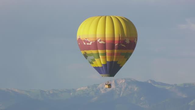 vídeos de stock e filmes b-roll de ms aerial ts zo ds shot of hot air balloon flying in sky over mountain range / jackson wyoming united states - balão de ar quente