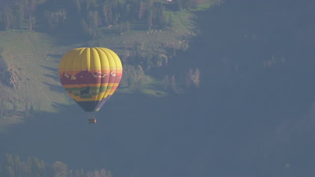 MS AERIAL TS Shot of hot air balloon with Teton Mountains / Jackson Wyoming United States