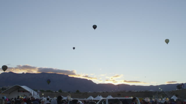 stockvideo's en b-roll-footage met ws shot of hot air balloons flying with mountains in back side during festival at sunrise / albuquerque, new mexico, united states - vijf dingen