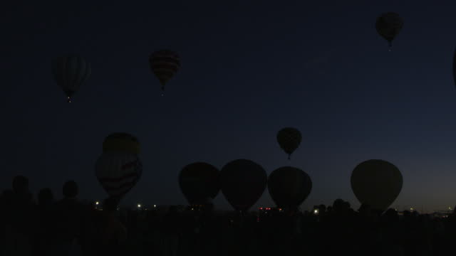 ms pan shot of hot air balloons illuminating and launching at dawn / albuquerque, new mexico, united states - medium group of objects stock videos & royalty-free footage