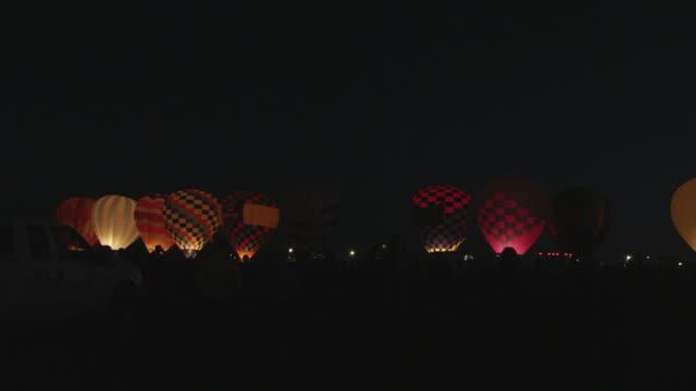 vídeos de stock, filmes e b-roll de ms pan shot of hot air balloons illuminating at dawn / albuquerque, new mexico, united states - grupo médio de objetos
