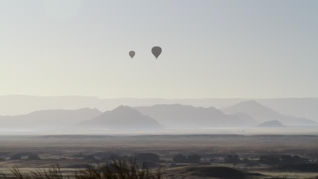 ws shot of hot air balloons moving in hazy sky on mountains / sossusvlei, hardap, namibi - wiese stock videos & royalty-free footage