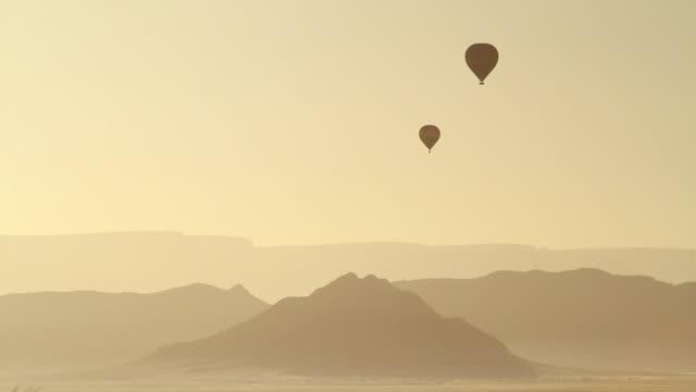 vidéos et rushes de ws shot of hot air balloons moving in hazy sky on mountains / sossusvlei, hardap, namibi - wiese