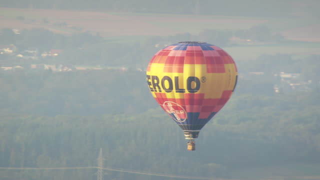 MS AERIAL TS ZI Shot of hot air baloon flying over hils and farmfield / Germany