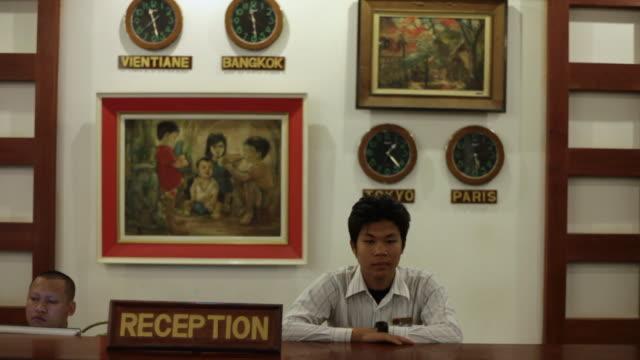 vidéos et rushes de ms shot of hotel reception attendees standing behind desk / vientiane, laos - réception d'hôtel
