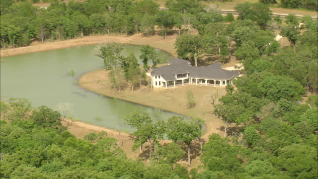vídeos de stock e filmes b-roll de ms aerial ts shot of house surrounded by trees near small lake / texas, united states - rodear
