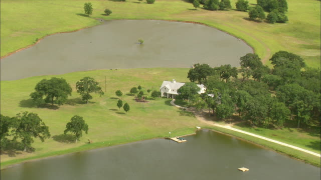 vídeos de stock e filmes b-roll de ms aerial ts shot of house surrounded by trees near two small lake / texas, united states - rodear