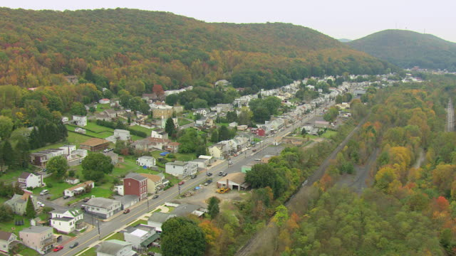 MS AERIAL Shot of houses and main road nestled in between hills / Mechanicsville, Pennsylvania, United States