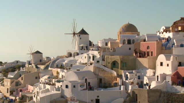 ms shot of houses and windmills at village oia / santorini, cyclades, greece - oia santorini video stock e b–roll