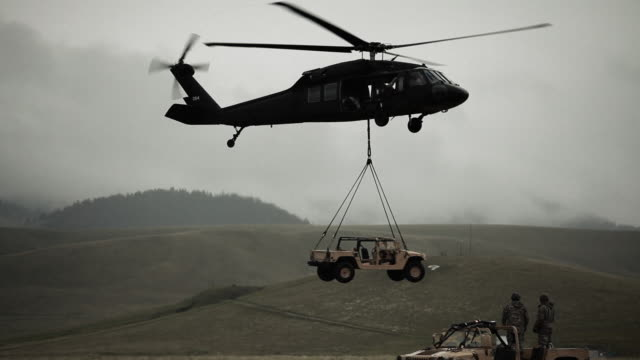 shot of humvee being set down by black hawk helicopter in field. - helicopter landing stock videos & royalty-free footage