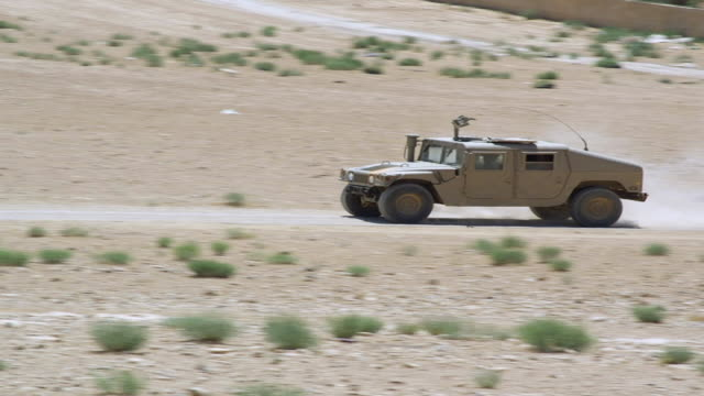 stockvideo's en b-roll-footage met ms ts tu shot of humvee running on desert road and village in distance / desert town, jordan - humvee