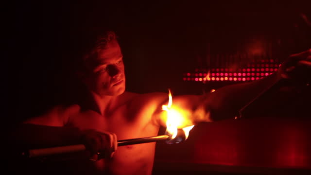 cu ts pan shot of hunky male stripper performing with fire / london, united kingdom - strip stock-videos und b-roll-filmmaterial