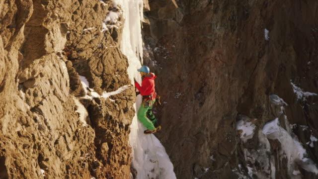 vídeos y material grabado en eventos de stock de ms pan shot of ice climber going up steep pillar of ice surrounded by rock and snow / cody, wyoming, united states - artículo de montañismo